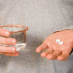 thinkstock_rf_man_holding_glass_of_water_and_pills